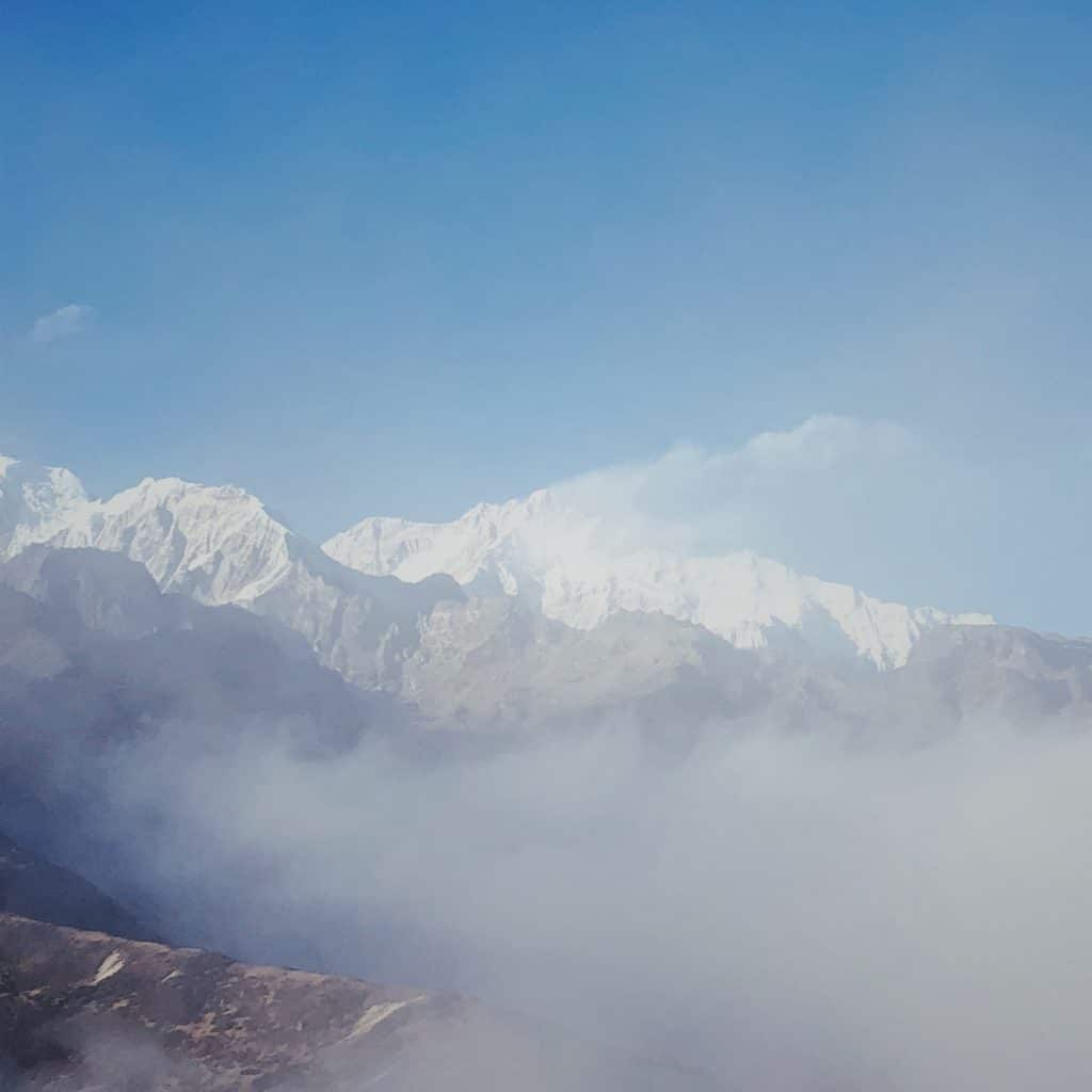 Mount Kanchenjunga, shrouded in fog, with a snow plume blown off the summit.